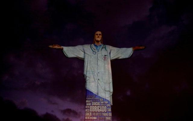 """의료진의 모습이 투영된 예수상. 포르투갈어를 비롯해 다양한 나라의 말로 """"감사합니다""""라고 쓰여있다."""